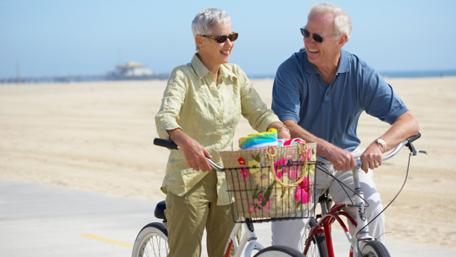 an elderly couple riding bikes on the beach