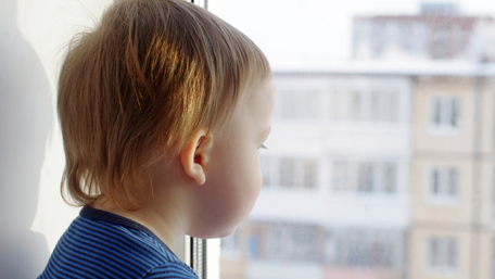 a toddler looking out a wiindow