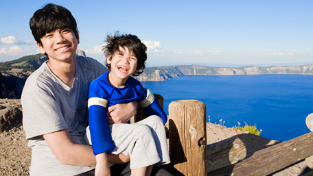 Big brother holding disabled little boy by Crater Lake